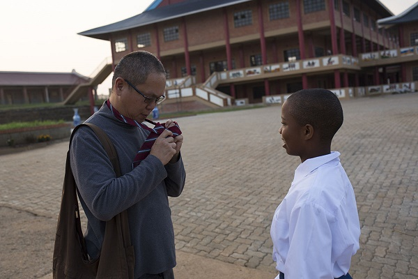 Acting Director, KC Tan adjusts a tie for student Lindokuhle Dludlu before breakfast at Amitofo Care Centre, Swaziland. Dludlu is in high school, the centre deosn't have a high school up and running as yet, so the students head to a local school by bus every morning at around 6:30am. Once back from school they catch up on their Chinese Mandarin language studies as well as other homework. Tan, originally from Singapore was at a Buddhist class and was told about Amitofo and wanted to volunteer. He got in touch with them and is now one of the directors at the Swaziland centre. CORNELL TUKIRI © 03 March 2017